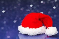 Small Santa hat on white sparkle background. Royalty Free Stock Photo