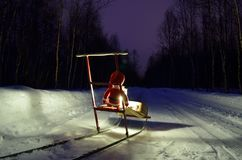 Small santa travelling home on kicksled on snowy road with suitcase and lantern Royalty Free Stock Photography