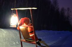 Small santa travelling home on kicksled on snowy road with suitcase and lantern Royalty Free Stock Image