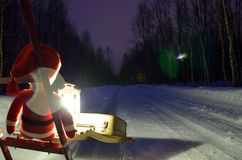 Small santa travelling home on kicksled on snowy road with suitcase and lantern Stock Images