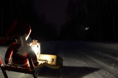 Small santa travelling home on kicksled on snowy road with suitcase and lantern Stock Photos
