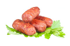 Small sausages. On a white background with green parsley Stock Photos