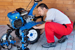 Small scale agriculture - man checking on small motorized tiller Royalty Free Stock Photo