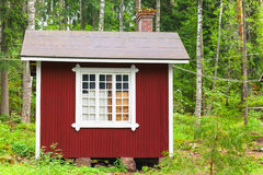 Small Scandinavian red wooden house in forest. Small Scandinavian red wooden house over green forest background. Kotka, Finland Stock Photo