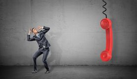 A small scared businessman on concrete background near a large red retro phone handle hanging down. Stock Image