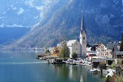 Small scenic village with snowy mountain on the background. Hallstatt waterfront with a great view of snowy mountain on the back Stock Photo