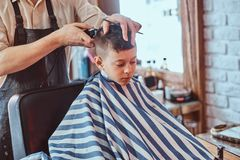 Small school boy is getting trendy haircut from expirienced barber at modern barbershop. Young school boy is getting trendy hairstyle from expirienced royalty free stock photo