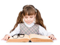 Small schoolgirl reading big book. isolated on white background Royalty Free Stock Images