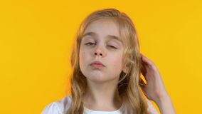 Small schoolgirl thinking, shrugging shoulders remembering necessary information. Stock footage stock video