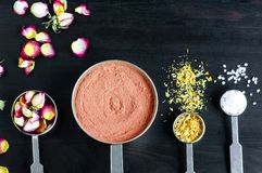 Small scoops with moroccan red clay, dry rose buds, marigold flowers and dead sea salt. Ingredients for preparing diy masks. royalty free stock photo