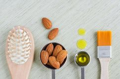 Small scoops with raw almonds, almond oil, wooden hair brush and cosmetic brush. Ingredients for preparing diy masks. Small scoops with raw almonds, almond oil stock photo