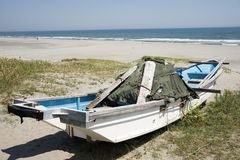 Boat on a sandy beach. A small scraped boat on a sandy beach under blue sky Stock Images