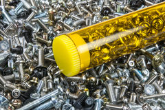 Small screws in the box. A lot of screws on the background and nice yellow box on foreground Royalty Free Stock Images