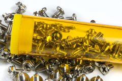 Small screws in the box. Small screws in yellow box on white background Stock Photos