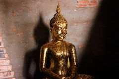 Small sculpture of Buddha with the offering of golden leaves wai phra at Ayutthaya, Thailand. stock photography