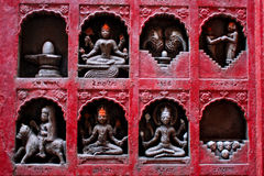 Small sculptures of Hindu gods, lovers and skulls. On the wall of the old temple in Varanasi, India stock image