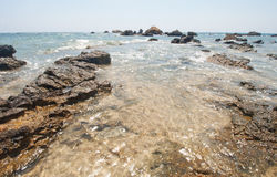 A small sea bight on the island. Sea waves. Coastline. Stones in the water. The sea breakdown. Warm wind. Sunny weather. Sand and stones Royalty Free Stock Images