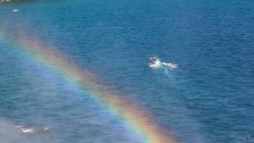 Small boat and rainbow at sea. Small sea boat passing near the rainbow coming from Karpuzkaldiran also known as Duden waterfall stock footage