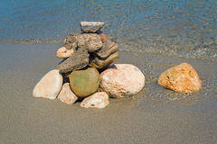 Small sea stones on the seashore, covered with a sea wave. Stock Photography