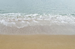 Small sea wave on a sandy beach Stock Image