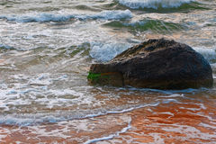 Small sea waves breaking on a rock Stock Photo