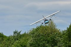 Small seaplane in low flight over trees 1 Stock Photo