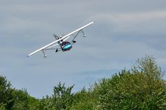 Small seaplane in low flight over trees Stock Images