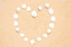 Small seashells in the shape of a heart on a smooth sandy beach. royalty free stock image