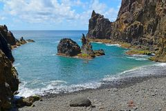 A small secluded pebble beach surrounded by rocks, Praia do Zimbralinho, Porto Santo, Madeira, Portugal Royalty Free Stock Images