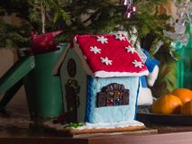Small self-made gingerbread house under new year tree close-up, selective focus, shallow DOF stock image