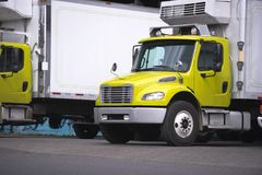Small semi truck with box trailer and refrigeration unit for loc. Al delivery of cooled food stand for relevant safety carry standing at warehouse dock for Royalty Free Stock Photos
