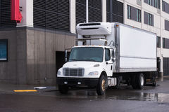 Small semi truck with reefer unit on box trailer for local delivery unloading delivered food