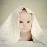 Small serious baby with Down syndrome hid under blanket Stock Images