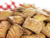 Small sesame cheese pies. A close up of small sesame pies filled with feta cheese on a traditional red-and-white squared napkin decorated with some wheat stock images