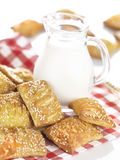 Small sesame cheese pies. Small sesame pies filled with feta cheese on a traditional red-and-white squared napkin decorated with a jug full of fresh milk stock photo