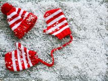 Snow covered small red and white stripped hat with mittens royalty free stock image