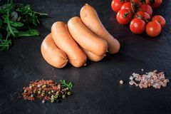 Small set of raw short sausages with rucola and tomatoes. Small set of raw short thick sausages with pink salt, spices, green rucola and tomatoes cherry on black stock images