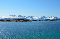 Small settlement on sea islands with snowy mountains Stock Photos