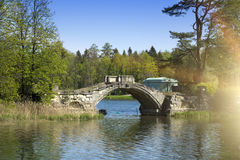 Small shabby bridge in park over a pond Stock Photo