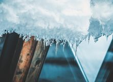 Ice icicles hanging from roof of house. Royalty Free Stock Images
