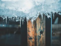 Ice icicles hanging from roof of house. Stock Image