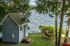 Life is better by the lake in the summer. Small shed lakeside with a wooden swing in the summer shade Royalty Free Stock Photo