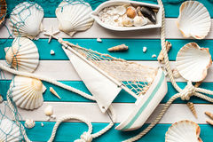 Small ship, boat, fishing net, shells and sailor rope on a wooden background. Sea concept. Overhead view. Royalty Free Stock Photo