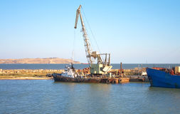Small ship and crane in dock Stock Photos