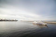 Small ship entering a harbor Royalty Free Stock Photography