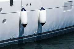 Small ship fenders hanging above white yacht hull Stock Image