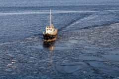 Small ship floating in the water among the ice floes Stock Images