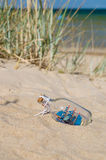 Small ship in the glass bottle lying on the beach. Souvenir concept Royalty Free Stock Photos