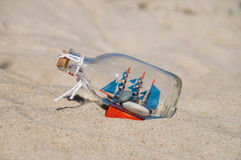 Small ship in the glass bottle lying in the sand Royalty Free Stock Image