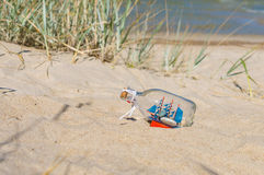 Small ship in the glass bottle lying on the sandy beach. Souvenir concept Stock Image